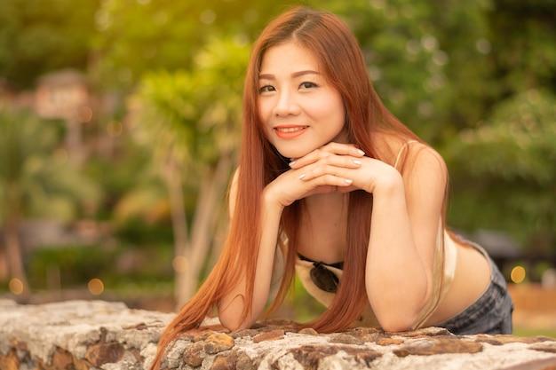Femme asiatique debout, souriant et regardant dans les yeux.
