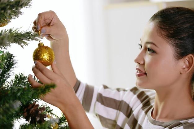Femme asiatique décorant le sapin de noël.
