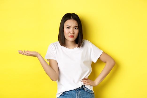 Femme asiatique déçue demandant si, lever la main et regarder la caméra sceptique, debout sur le jaune.