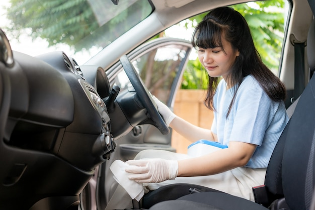 Femme asiatique désinfectant le changement de vitesse de voiture par des lingettes jetables désinfectantes de la boîte. prévenir le virus et les bactéries, prévenir le covid19, le virus corona,