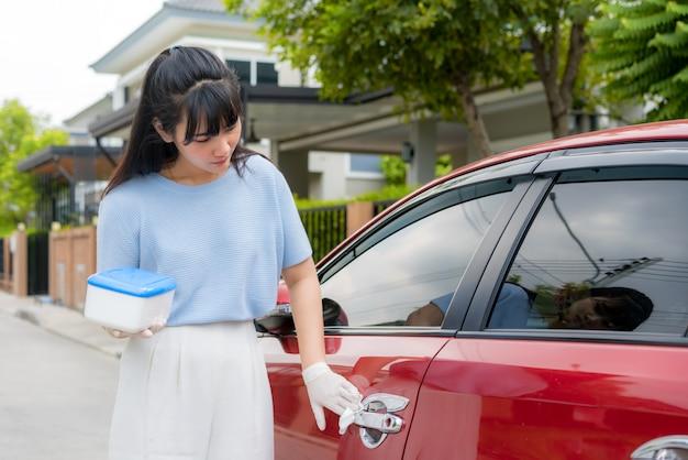 Femme asiatique désinfectant la poignée de porte de voiture rouge par des lingettes jetables désinfectantes de la boîte. empêcher le virus et les bactéries, empêcher covid19, virus corona, alcohol sanitizer. concept d'hygiène à la maison.