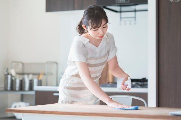 Femme asiatique, désinfection, maison, table manger, à, aérosol
