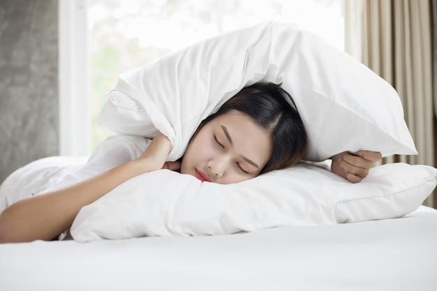 Femme asiatique déteste se réveiller tôt le matin. fille endormie regardant le réveil et essayant de h