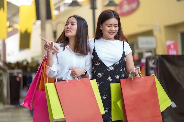 Femme asiatique, deux personnes, apprécier, achats, à, les, centre commercial