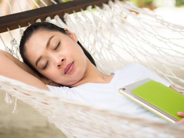 Femme asiatique dormir sur un hamac avec la main tenant la tablette sur la plage.