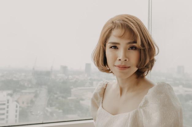 Une femme asiatique douce et douce porte une robe blanche
