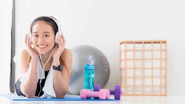 Femme asiatique écoutant de la musique avec un casque après avoir joué au yoga et fait de l'exercice à la maison avec un espace de copie. exercice pour perdre du poids, augmenter la flexibilité et resserrer la forme.