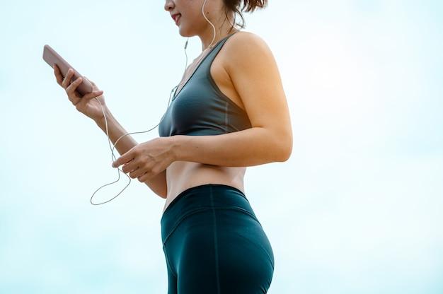 Une femme asiatique écoute de la musique depuis son téléphone portable en courant le matin.
