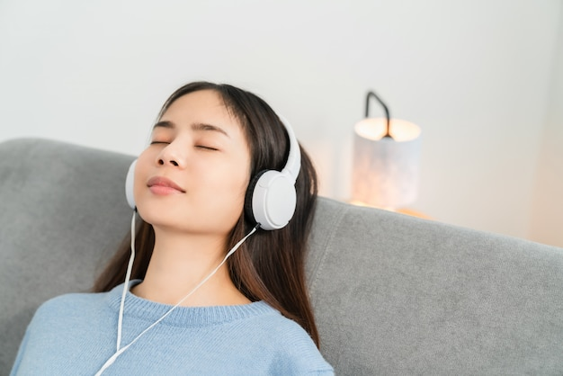 Femme asiatique, écouter de la musique et assis sur le canapé