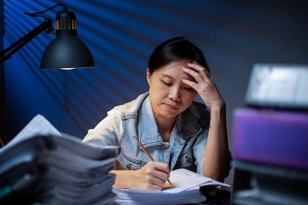 Femme asiatique écrivant des documents en heures supplémentaires la nuit. délai de travail au bureau. mal de tête de fille d'officier et occupé avec son travail. malheureux et stress.