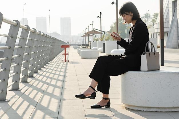 Femme asiatique élégante assise à l'extérieur