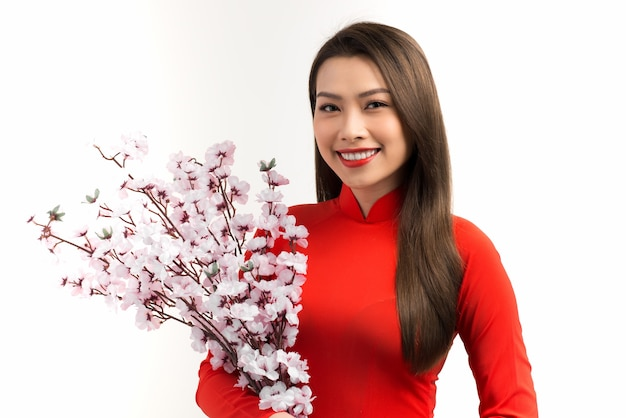 Femme asiatique élégante tenant des fleurs de pêche tout en portant ao dai sur blanc.