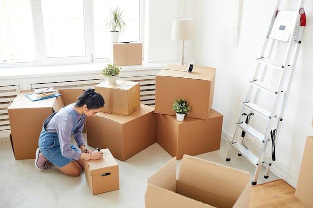 Femme asiatique emballant des boîtes en carton dans une salle blanche vide, déménagement, déménagement et concept de décoration de maison