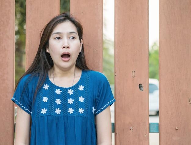 Femme asiatique avec émotion visage effrayé sur fond de clôture en bois floue