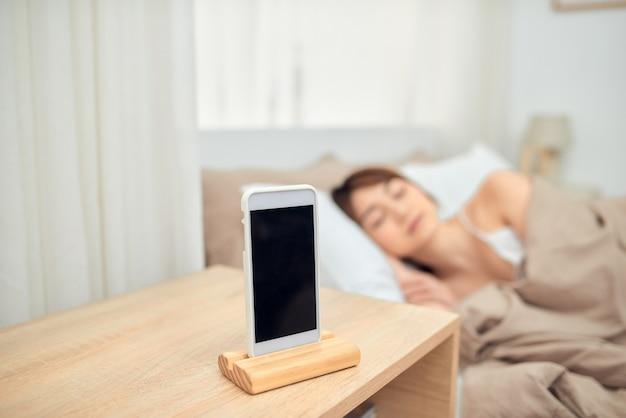 Femme asiatique endormie dans son lit réveillé par alarme sur téléphone mobile