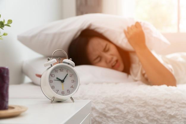 Femme asiatique endormie qui dort sur le lit et utilise un oreiller pour fermer l'oreille