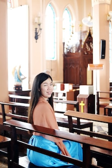 Une femme asiatique est assise sur une chaise en bois et sourit pour prier dieu dans une église chrétienne de faire un vœu d'espoir et d'encouragement dans la vie. rituels et croyances dans le concept chrétien de thaïlande.