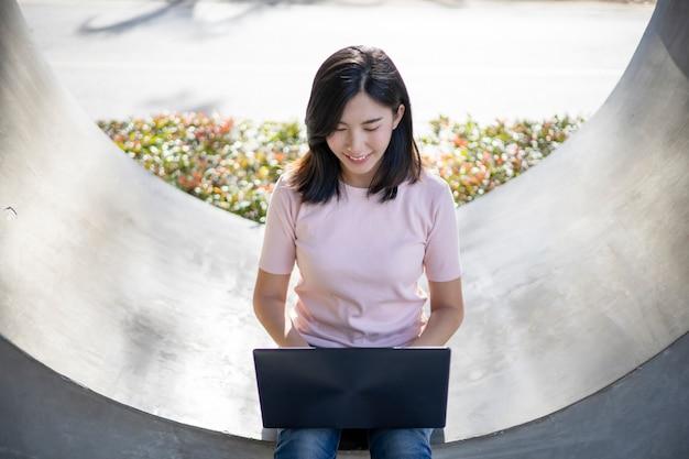 Une femme asiatique est assise sur un ordinateur portable.