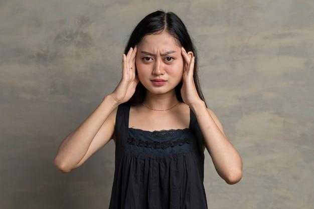 Femme asiatique est debout mal de tête sur le fond