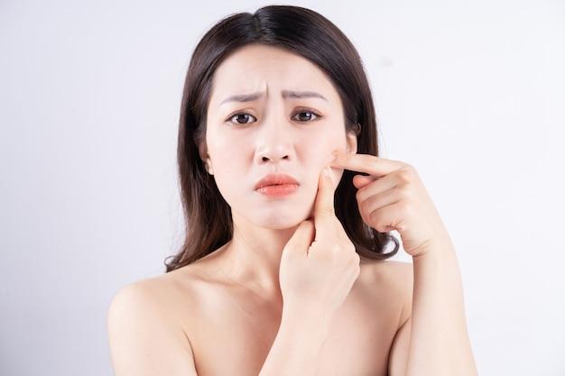 Une femme asiatique est mal à l'aise avec l'acné sur son visage