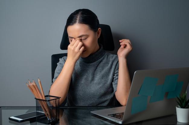 Une femme asiatique était malade avec des douleurs oculaires, touchant ses yeux, travaillant sur un ordinateur portable au bureau