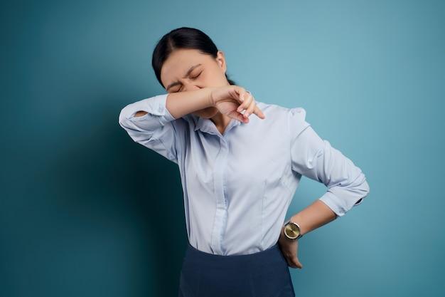Une femme asiatique était malade de fièvre isolée sur bleu.