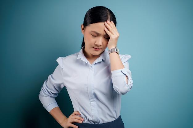 Une femme asiatique était malade avec des maux de tête touchant sa tête isolée sur bleu.