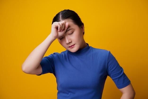 Une femme asiatique était malade avec des maux de tête touchant sa tête en jaune.