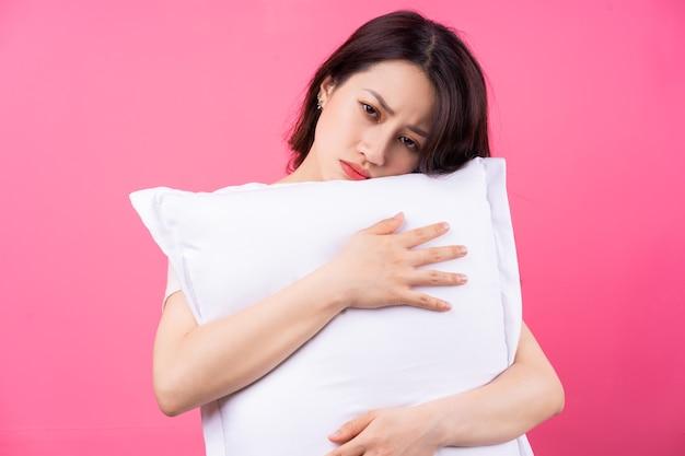 Femme asiatique, étreindre, oreiller, sur, rose
