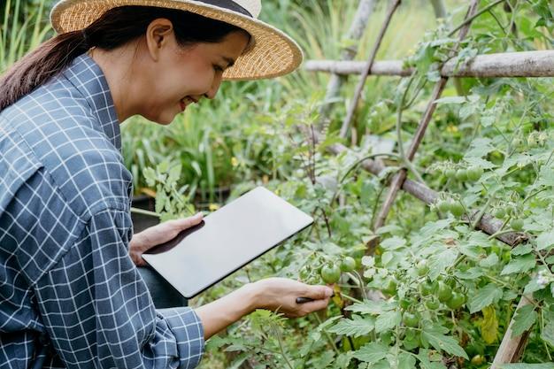 Femme asiatique étudiant différentes plantes avec une tablette