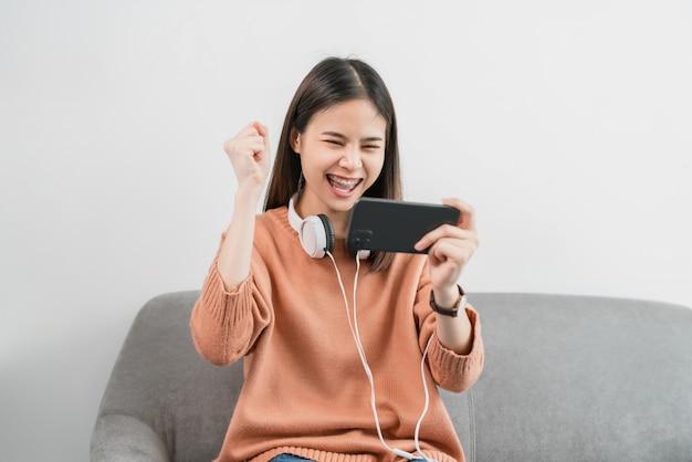 Femme asiatique excitée à jouer à des jeux sur le smartphone dans le salon