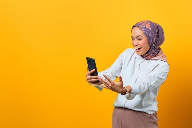 Femme asiatique excitée regardant smartphone obtenir de bonnes nouvelles sur fond jaune