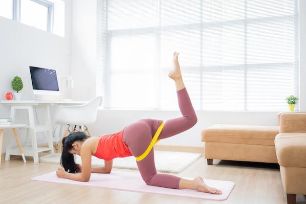 Femme asiatique exerçant à la maison sur un tapis de yoga.