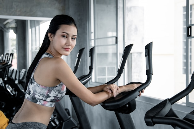 Femme asiatique exerce avec le cardio dans la salle de gym.