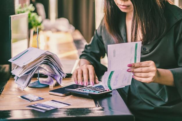 Femme asiatique avec des factures financières, calcul de la dette