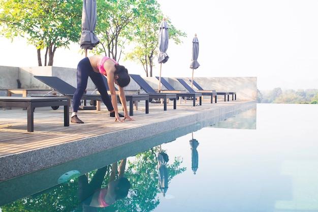 Femme asiatique, faire du yoga près de la piscine. concept santé et beauté