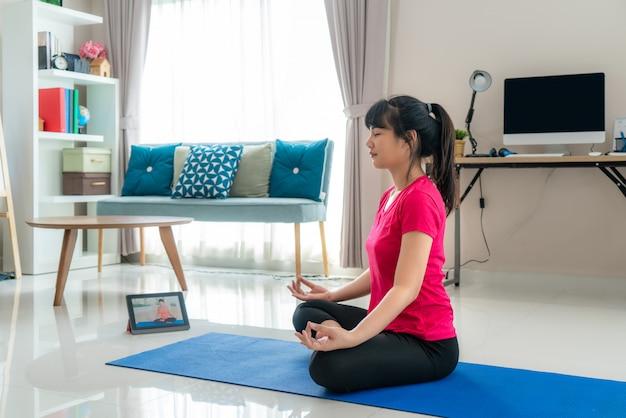 Femme asiatique faisant des exercices de yoga pour s'éloigner de leurs ordinateurs pour faire de l'exercice à la mi-journée