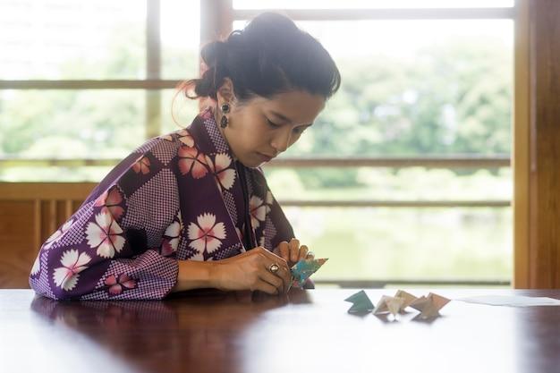 Femme asiatique faisant de l'origami avec du papier japonais