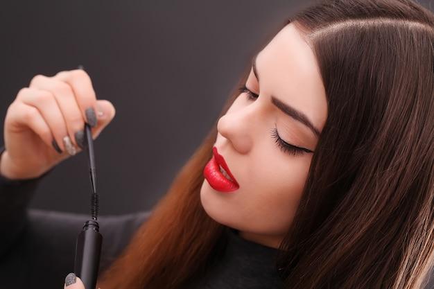 Femme asiatique fait son maquillage mascara cils sombre.