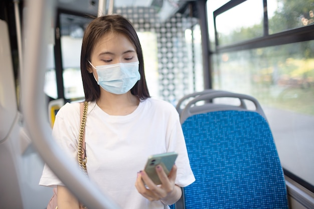 Une femme asiatique fait un tour dans le bus ou le tram des transports publics.