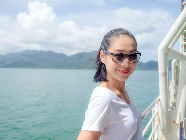 Femme asiatique sur le ferry en regardant la vue sur la mer.