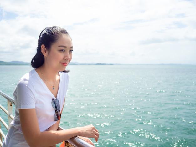 Femme asiatique en ferry en regardant la vue sur la mer
