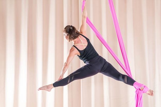 Femme asiatique de formation dans la salle de fitness avec des éléments de yoga mouche