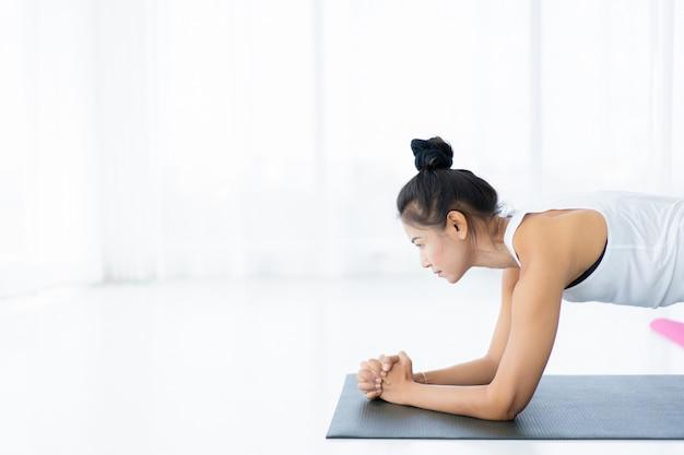 Femme asiatique forte faisant un exercice dans la salle près de la fenêtre avec un éclairage naturel, femme bordée par terre, beau portrait de femme asiatique.