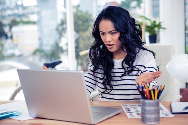 Femme asiatique fronçant regardant un ordinateur portable au bureau
