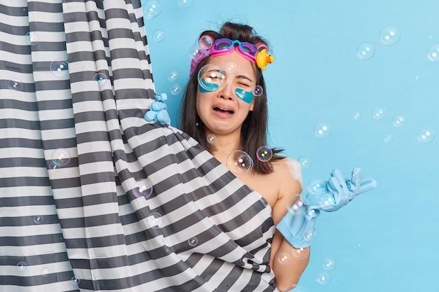 Une femme asiatique frustrée et mécontente applique des patchs sous les yeux pleure de désespoir prend une douche fatiguée après le travail fait des poses de coiffure parfaites derrière un rideau à rayures