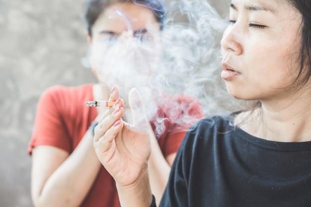 Femme asiatique fumant une cigarette à proximité de membres de la famille