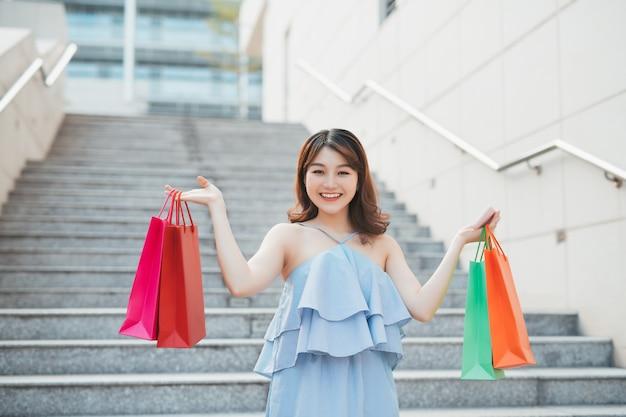 Femme asiatique gaie descendant avec des paquets colorés de magasin