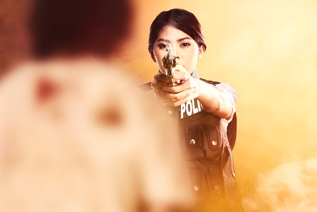 Femme asiatique en gilet de police avec une arme à la main prête à attaquer des zombies avec un arrière-plan dramatique