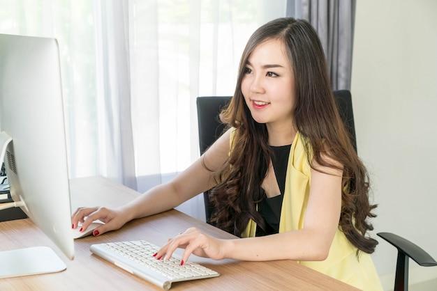 Femme asiatique heureuse au bureau